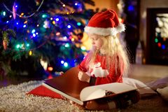 Happy little girl reading a story book by a fireplace in a cozy dark living room on Christmas eve Stock Photo