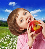 Happy little girl with red apple Royalty Free Stock Images