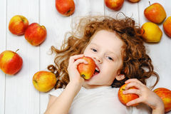 Happy little girl with red apples on light wooden floor. Top vie Stock Photos