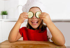 Happy little girl in red apron and cook hat playing in the kitchen with cucumber slices on eyes Royalty Free Stock Photography