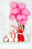 Happy little girl in a red dress with her gifts Stock Image