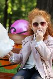 Happy little girl eats cotton candy. Happy little girl with red hair eats cotton candy on bench in summer green park Royalty Free Stock Images