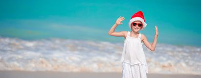 Adorable little girl in Santa hat on tropical beach royalty free stock image