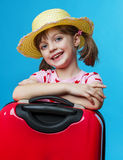 Happy little girl with a red suitcase Royalty Free Stock Photo