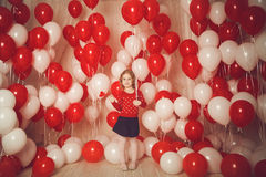 Happy little girl with red and white balloons Stock Photography