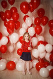 Happy little girl with red and white balloons Royalty Free Stock Photography