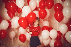 Happy little girl with red and white balloons Stock Image