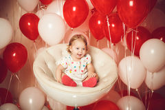 Happy little girl with red and white balloons Stock Images
