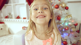 Happy little girl rejoices with a gift near the Christmas tree Royalty Free Stock Image