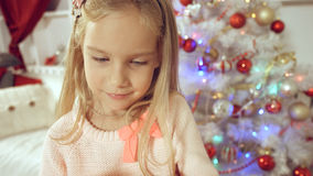 Happy little girl rejoices with a gift near the Christmas tree Royalty Free Stock Photos