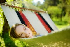 Happy little girl relaxing in hammock on beautiful summer day. Cute child having fun in spring garden. Family leisure at summer stock photos