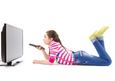 Happy little girl with remote control watching tv. Happy little girl with remote control laying down and watching tv Stock Image