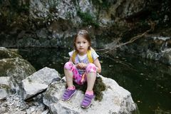 Happy little girl resting on a big rock by a small pond Stock Images