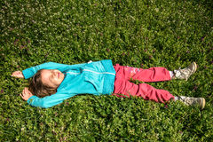 Happy Little girl resting on the grass Stock Photography