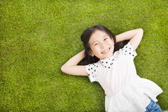 Happy Little  girl resting on the grass Royalty Free Stock Photos