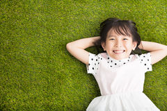 Happy Little  girl resting on the grass Royalty Free Stock Photo
