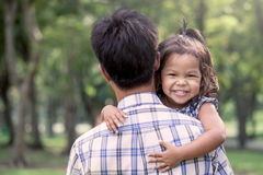 Happy little girl resting on her father's shoulder Stock Image
