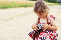 Happy little girl in retro outfit taking pictures with old film. Camera. Portrait of a cute preschool girl playing Royalty Free Stock Photo