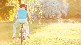 Happy little girl riding a bicycle on the meadow in summer sunshiny day. stock video footage