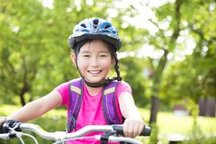 Happy girl  riding bicycle in the park Royalty Free Stock Photography