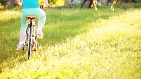 Happy little girl riding a bike in outdoor on green grass in the city park. stock footage