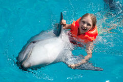 Happy Little Girl Riding the Dolphin in Swimming Pool. Little Smiling Girl Swimming with the Dolphin in the Swimming Pool in the Bright Sunny Day Stock Photo