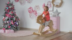 Girl rides toy rocking horse near christmas tree. Happy little girl riding toy rocking horse in the room in pink colors near the christmas tree in slow motion stock video footage