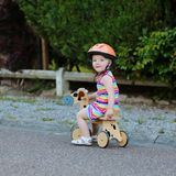 Happy little girl riding tricycle on the street Royalty Free Stock Photography