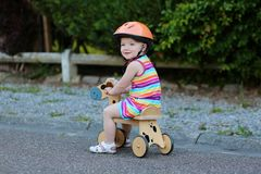 Happy little girl riding tricycle on the street Stock Photography