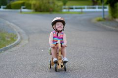 Happy little girl riding tricycle on the street Stock Photos