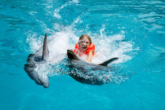 Happy Little Girl Riding two Dolphins in Swimming Pool. Little Laughing Girl Swimming with the Dolphins in the Swimming Pool in the Bright Sunny Day Stock Photos