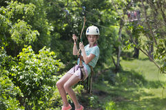 Happy little girl riding a zip line in a lush tropical forest. Happy smiling little girl riding a zip line in a lush tropical forest while on family vacation stock photo