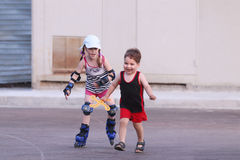 Happy little girl roller skates on asphalt and boy Stock Image