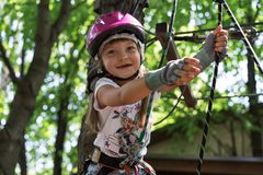 Happy little girl in a rope park in summer royalty free stock photography