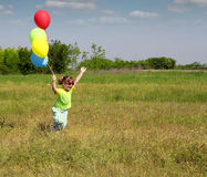 Happy little girl running. With balloons Royalty Free Stock Image