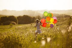 Happy little girl running across the field. With balloons Royalty Free Stock Photos