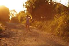 Happy little girl running along a country road Stock Photos