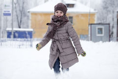 Happy little girl running on the background of snow covered wint Royalty Free Stock Photos