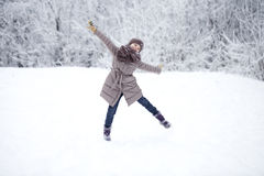 Happy little girl running on the background of snow covered wint Stock Photography