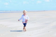 Happy little girl running on the beach Stock Photo