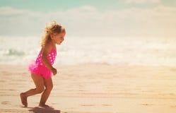 Happy little girl running on beach Stock Photo