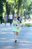 Happy little girl running in city park. Positive childish emitions stock photography