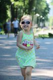 Happy little girl running in city park. Positive childish emitions royalty free stock image