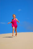 Happy little girl running down sand dunes. A beautiful happy smiling Caucasian girl child in a pink summer dress running down the sand dune in front of blue sky Stock Images