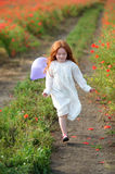 Happy little girl running on the field Royalty Free Stock Image