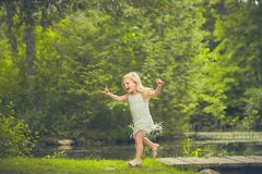 Happy little girl running in forest in summer. Portrait of happy little Caucasian girl wearing white dress running in forest in summer Royalty Free Stock Images
