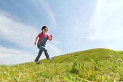 Happy little girl running on green summer field Royalty Free Stock Photos