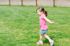Happy little girl running on green summer field Royalty Free Stock Image
