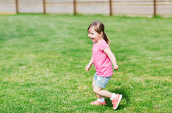 Happy little girl running on green summer field Stock Photography