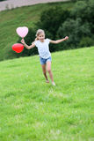 Happy little girl running holding balloons. Little girl running in field with balloons in one hand Royalty Free Stock Image